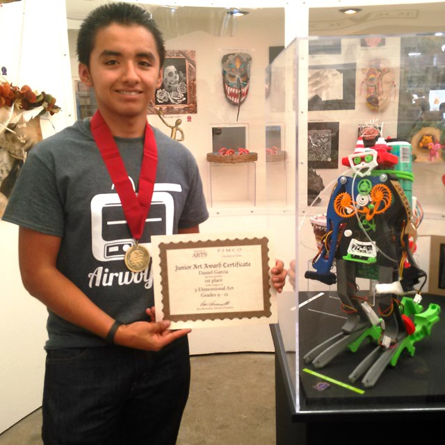 Daniel Garcia takes a photo with his 3-Dimensional Art achievement.